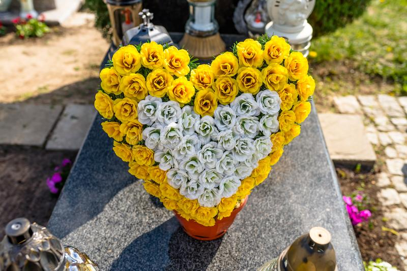 Artificial flowers in the shape of a heart and candlesticks lie on the tombstone in the cemetery. stock image
