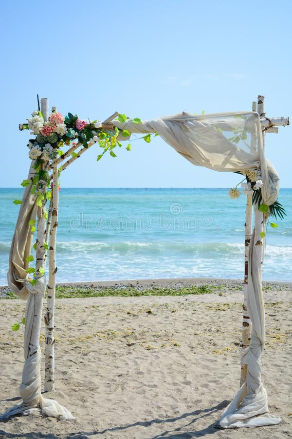Artificial Frame on a beach with white wood, flowers and nice tissue. In the background the blue sea with waves and gold sand royalty free stock photo