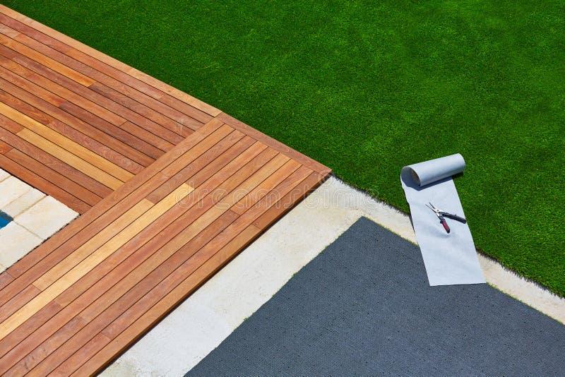 Artificial grass installation in deck garden with tools. Artificial grass turf installation in deck garden with tools and joint roll stock image