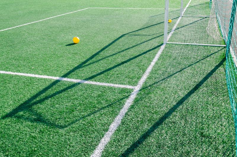 Artificial grass, white lines and soccer goal on a sunny day. Yellow balls on the grass stock photography