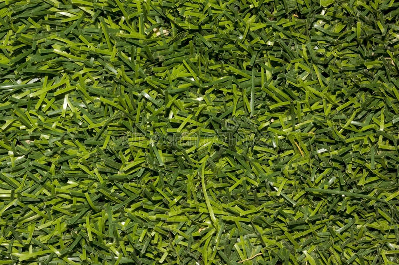 Artificial green grass. Artificial turf is a surface of synthetic fibers made to look like natural grass. It is most often used in arenas for sports that were stock photo