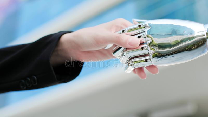 Artificial intelligence concept. Business people shake hands with ai robot royalty free stock photos