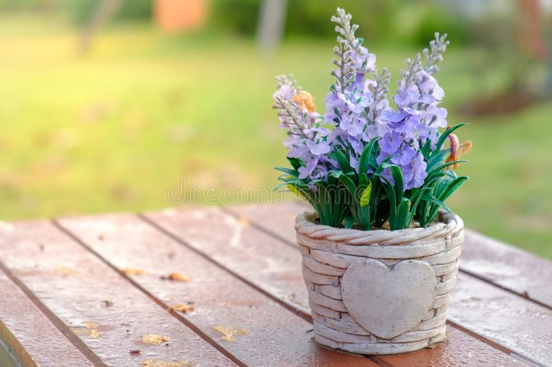 Artificial lavender flowers in metal vase on wood table stock image