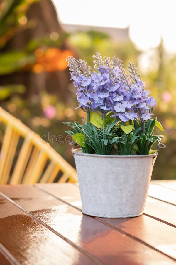 Artificial lavender flowers in metal vase on wood table royalty free stock images