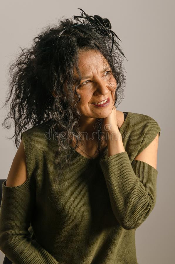 Artificial light portrait in studio, woman with long and curly h stock photo