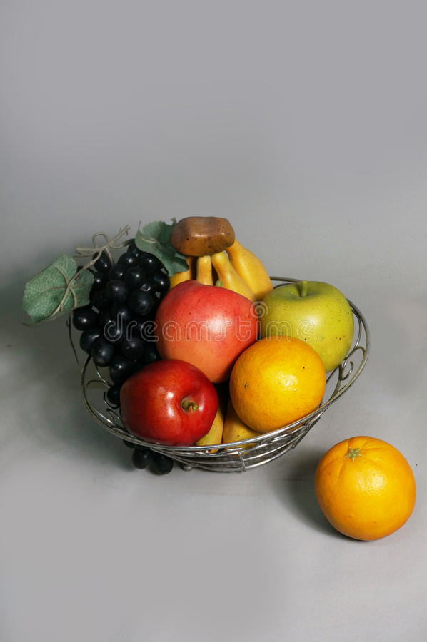 Artificial mixed fruits. Plastic, green and red apple, grape, orange, bananas on metal basket on gray background, close up royalty free stock photo