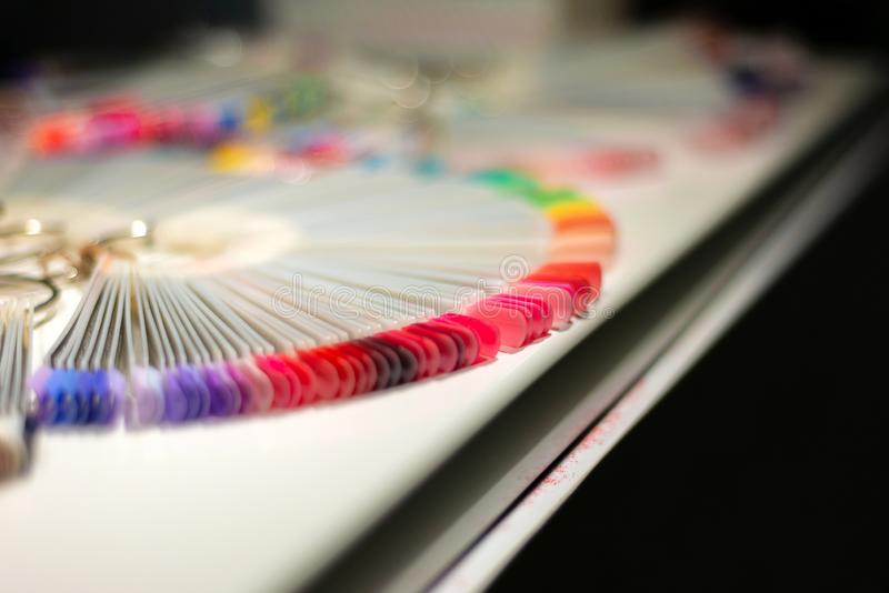 Artificial multi-colored designs for manicure on nails in a beauty salon stock photo