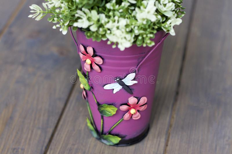 Artificial part of a green bush in a pink bucket with flowers and a butterfly on a wooden floor stock image