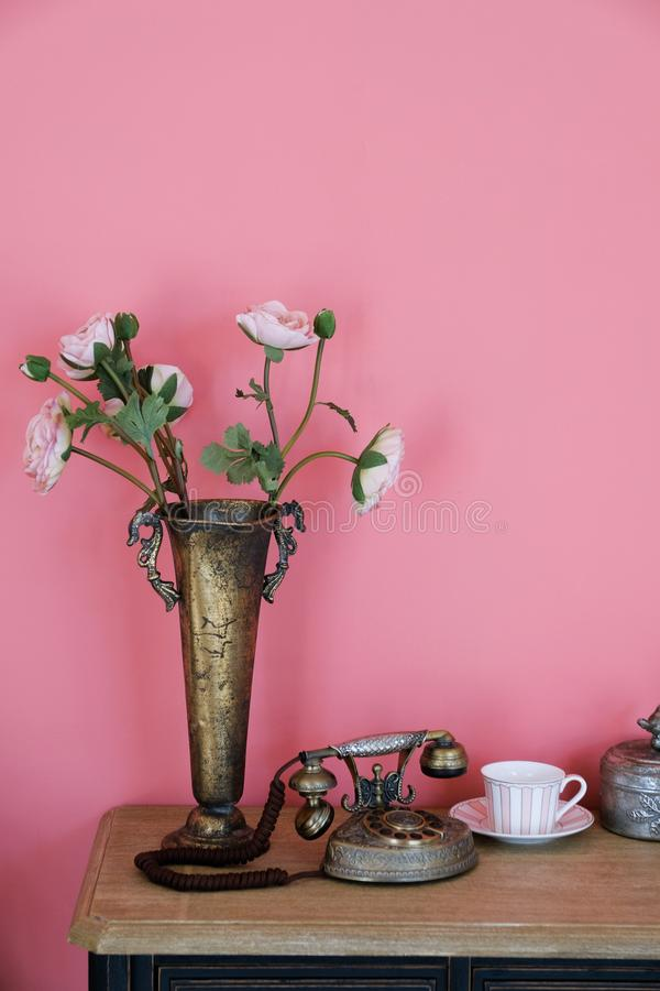 Artificial pink rose flowers in an old iron copper vase on a wooden table, against a pink wall. Near the old phone, a mug on a stock images