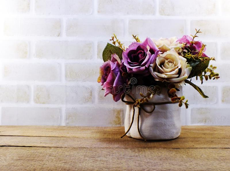 Artificial pink roses flowers in vase on wooden and space wallpaper. Artificial rose flowers in vase on wooden and space wallpaper royalty free stock image