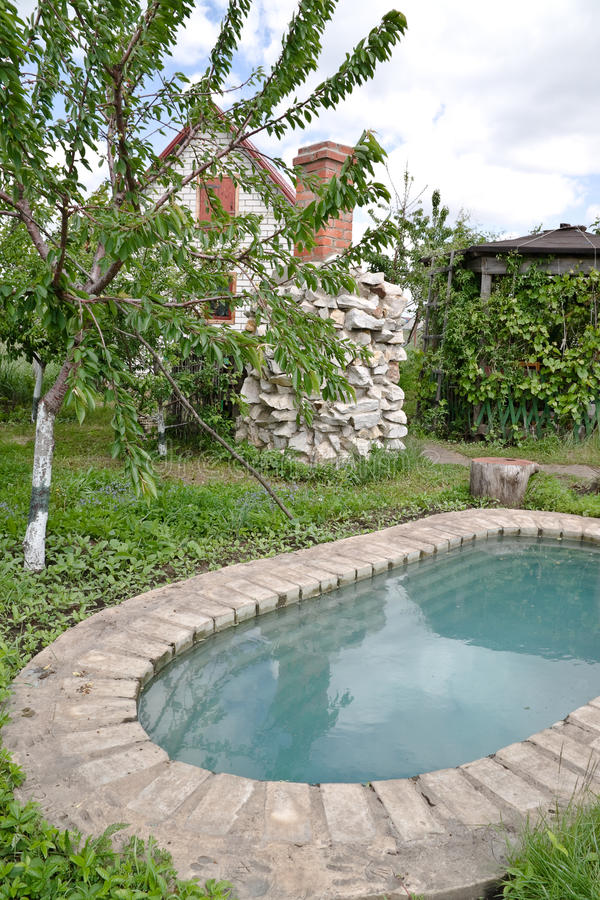 An artificial pond at the country dacha. Pond with water is element landscape royalty free stock image