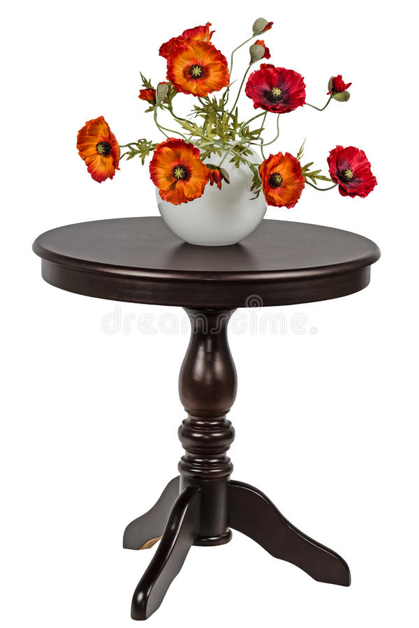 Artificial poppies in a vase on the round table royalty free stock photography
