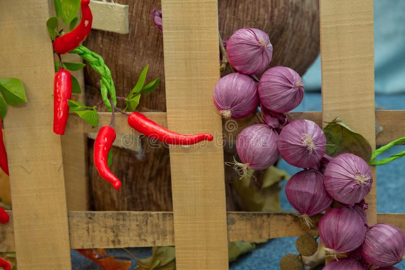 Wooden fence . Artificial red pepper, pink onion . Artificial fruits and vegetables on a blue background royalty free stock images