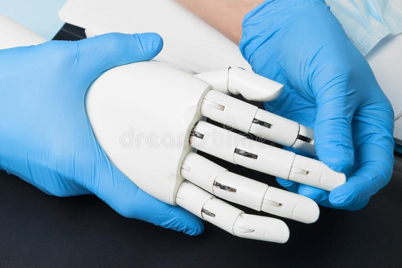Artificial robotic prosthesis. Doctor holds cyber hand.  royalty free stock photos