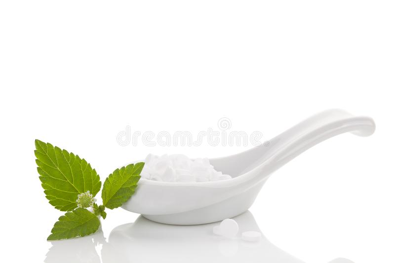 Artificial sweetener. Artificial sweetener pills in white spoon on white background and aztec sweet herb. Natural and artificial sugar. Carbs stock photos