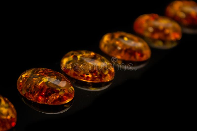 Artificial transparent amber cabochons on a black background closeup. Artificial amber cabochons on a black background macro royalty free stock photo
