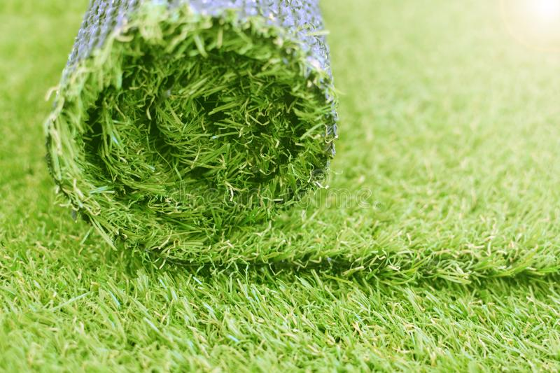 Artificial turf roll. Synthetic grass lawn laying background stock photo