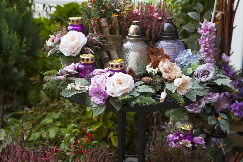 The Artificial and vibrant flowers, candles in purple tones by the day of the dead in Warsaw royalty free stock images