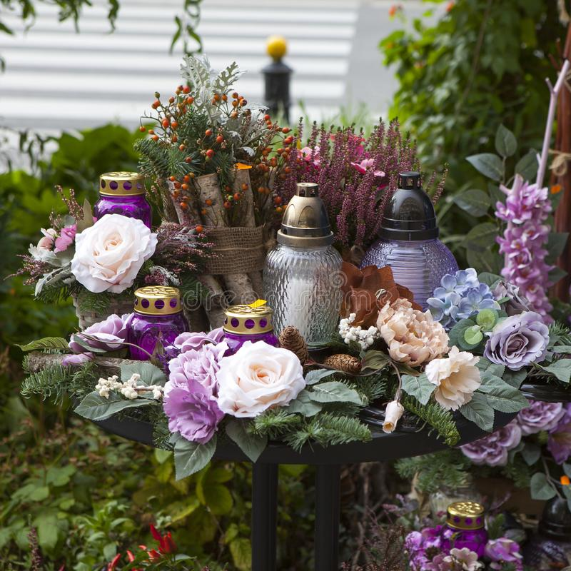 The Artificial and vibrant flowers, candles in purple tones by the day of the dead in Warsaw royalty free stock photography