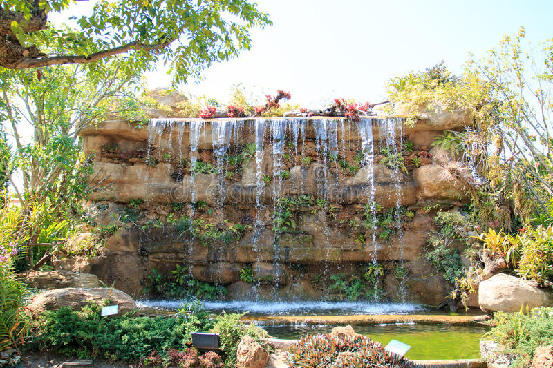 Artificial waterfall. In garden with light sky stock photography