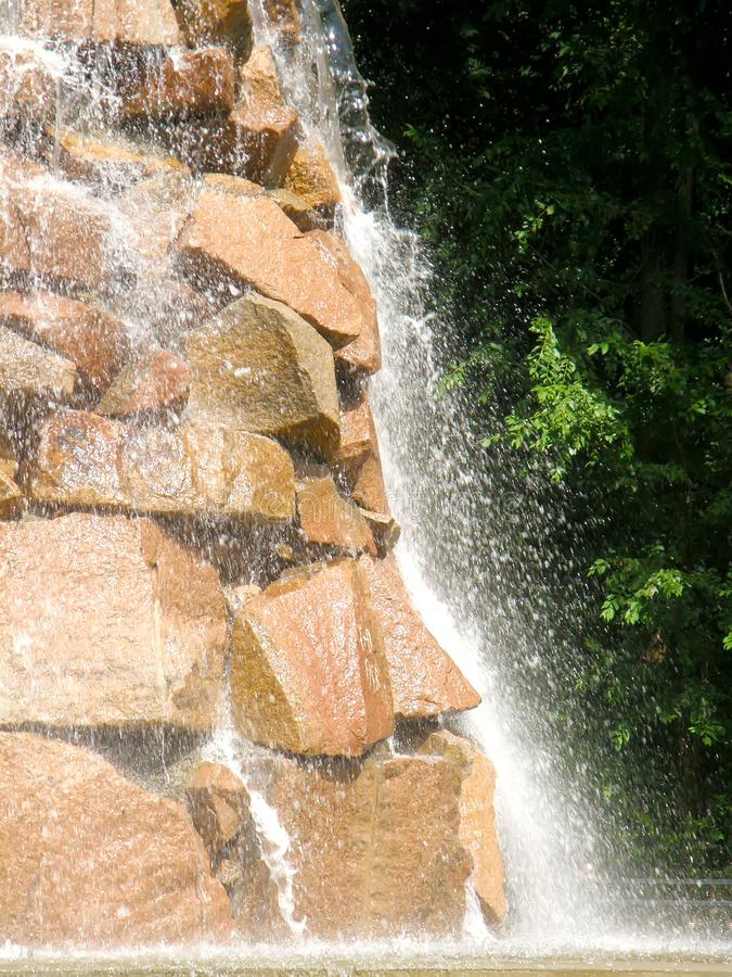 Artificial waterfall in a park on a pond royalty free stock images
