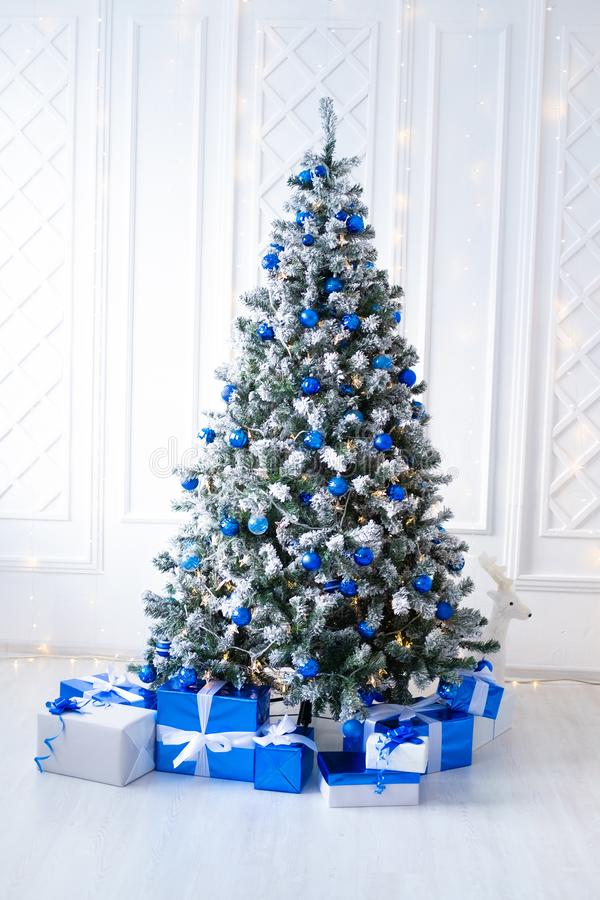 White Christmas Tree On White Decorated With Blue Ornaments And Garland Lots Of Presents Under The Tree Stock Image Image Of Interior Present 134602245