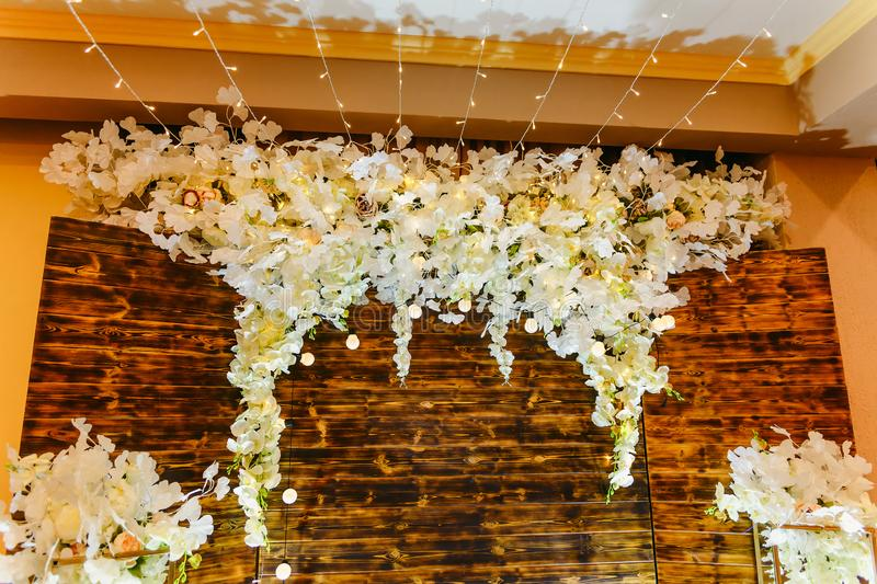 Artificial white flowers on the wall. Wedding decor royalty free stock photography