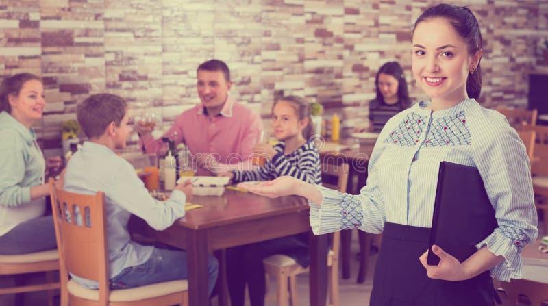 Artig ung servitris som välkomnar varmt gäster till familjkafét fotografering för bildbyråer