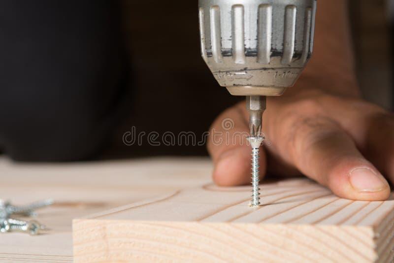 Artigiano che lavora con un cacciavite elettrico, fine su fotografie stock