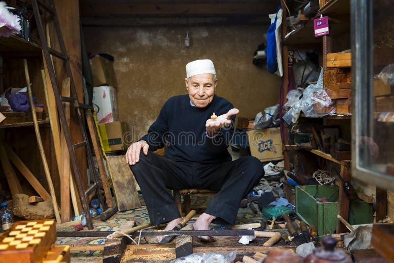 Artigiano che mostra una trottola nel suo negozio a Fes Medina fotografia stock libera da diritti