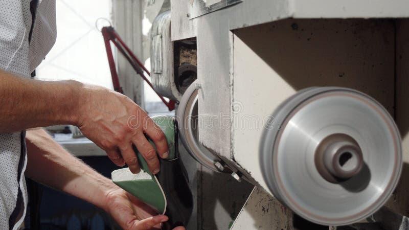 Artigiano che per mezzo della macchina della smerigliatrice mentre facendo le scarpe immagini stock