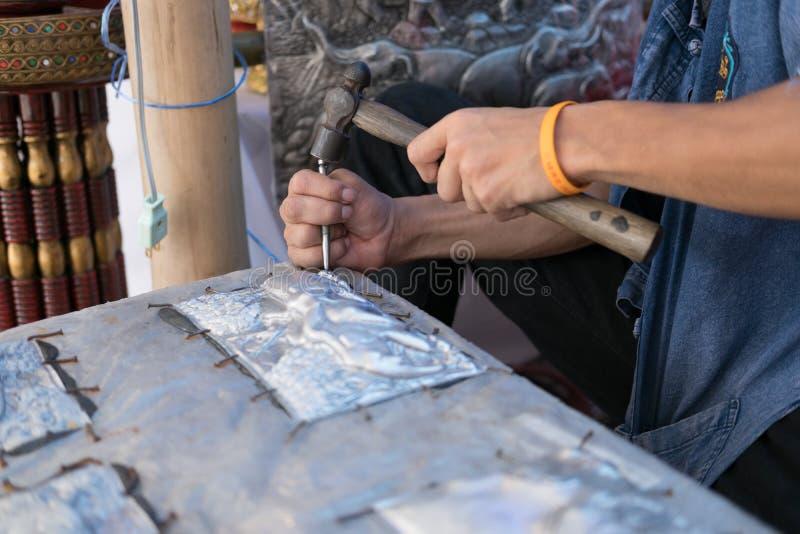 Artigiano di Silversmith che scolpisce elefante su un piatto d'argento (metallo immagine stock