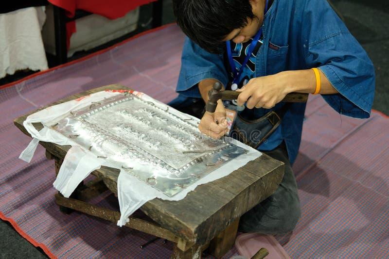 Artigiano di Silversmith che scolpisce modello sul piatto d'argento inglese del metallo immagini stock