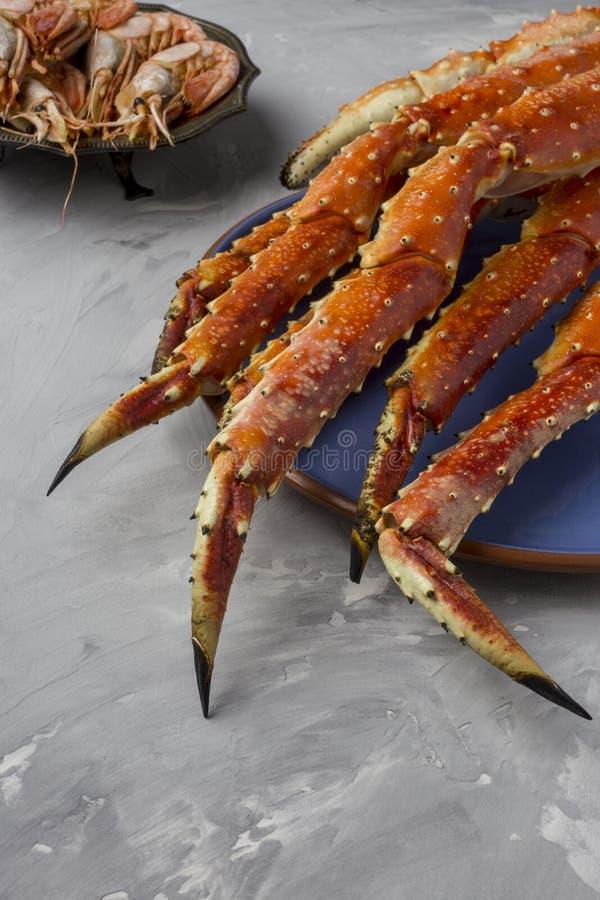 Artiglio di re Crab sul piatto blu a fondo grigio immagini stock libere da diritti