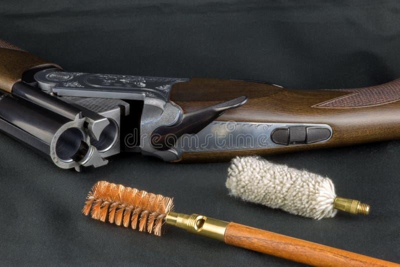 Artigos da limpeza da espingarda e da arma em uma tabela do repes imagem de stock