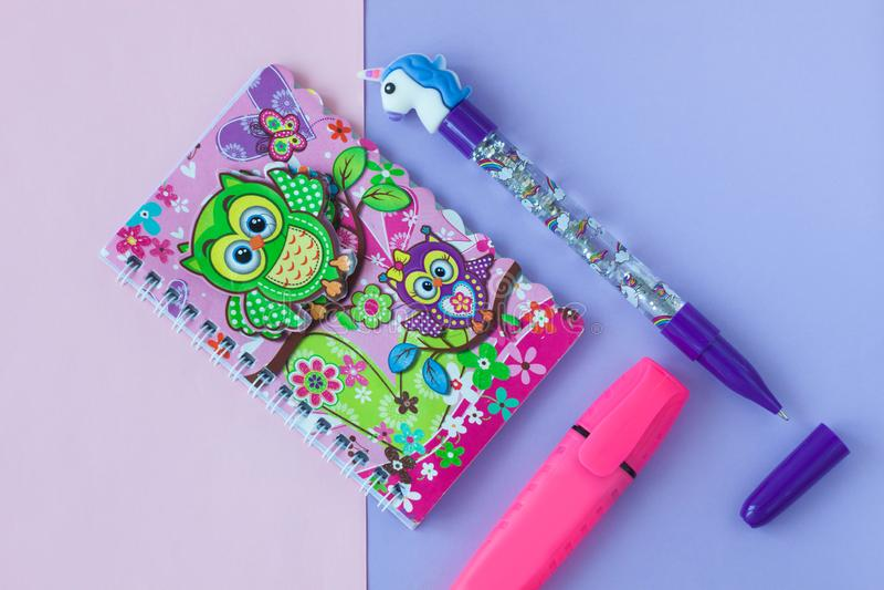 Artigos de papelaria da escola com a pena à moda do unicórnio e caderno da sucata da coruja em um rosa e em um fundo roxo do duot imagem de stock