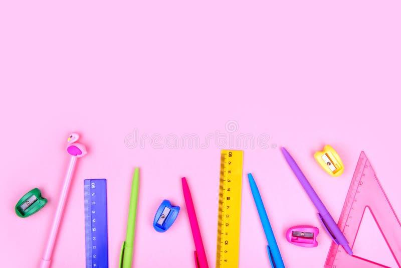 Artigos de papelaria da escola em um fundo cor-de-rosa imagens de stock