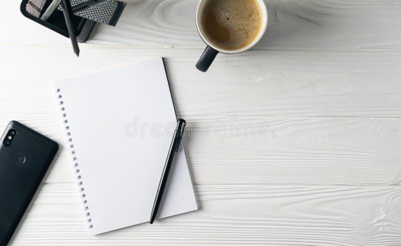 Artigos de papelaria do negócio do escritório que incluem o café, caderno, pena, telefone imagens de stock