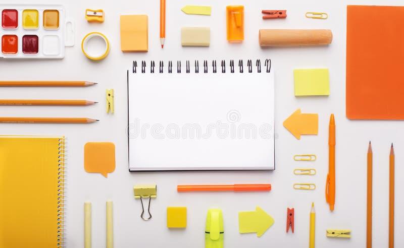 Artigos de papelaria e bloco de notas coloridos alaranjados do escritório no branco fotografia de stock