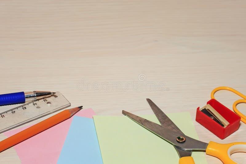 Artigos de papelaria que encontram-se em uma tabela de madeira com a borda fotos de stock royalty free