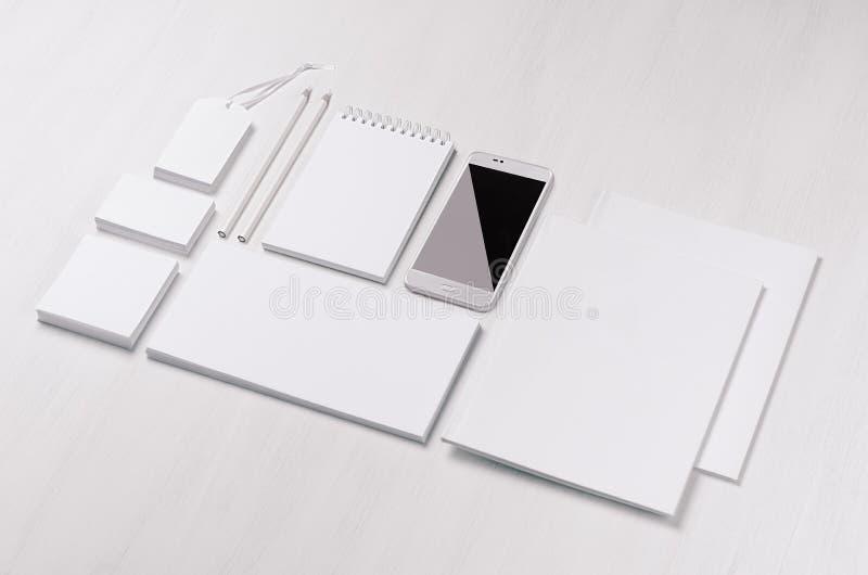 Artigos de papelaria vazios brancos - a etiqueta, bloco de notas, cabeçalho, envolve, telefona na prancha de madeira branca macia fotos de stock