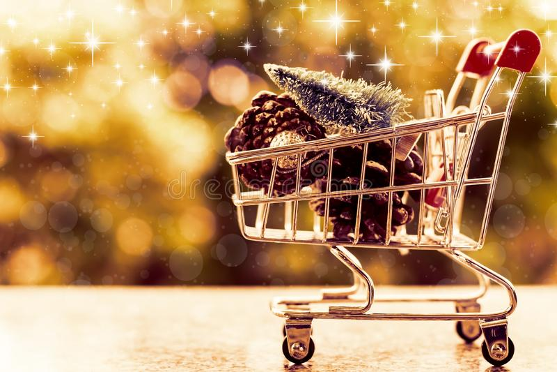 Artigos decorativos do Xmas no mini carrinho de compras ou trole contra b foto de stock