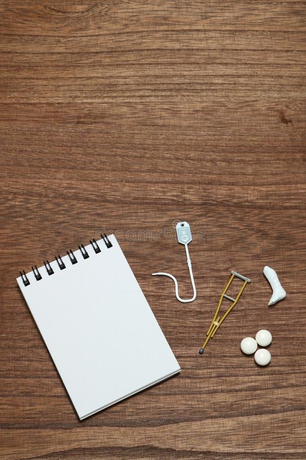 Artigos diminutos da doença ou do ferimento ao lado da almofada de memorando imagem de stock