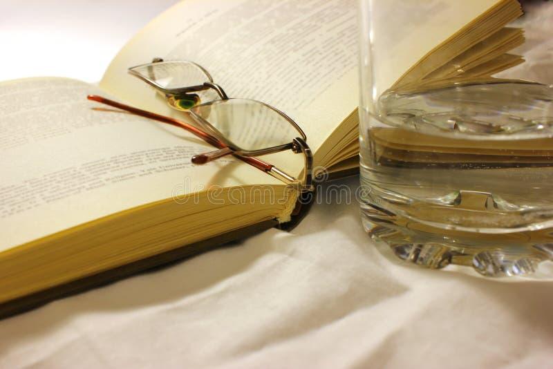 Artigos do lazer, vidros, livro, bebida situada no pano tecido fotos de stock royalty free