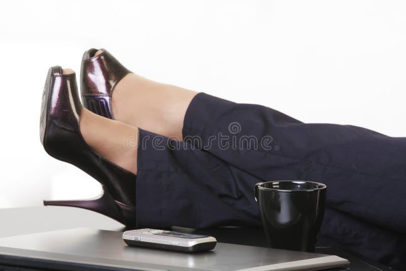Artigos do negócio e pés da mulher foto de stock