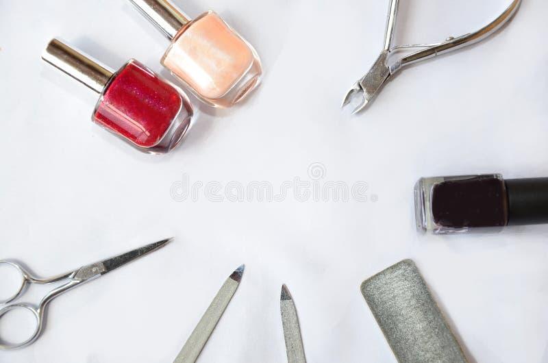 Artigos do tratamento de mãos no fundo branco, verniz para as unhas, arquivo, pregos imagem de stock
