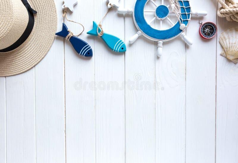 Artigos marinhos no fundo de madeira Objetos do mar: chapéu de palha, roupa de banho, peixe, escudos Configuração lisa, espaço da fotografia de stock