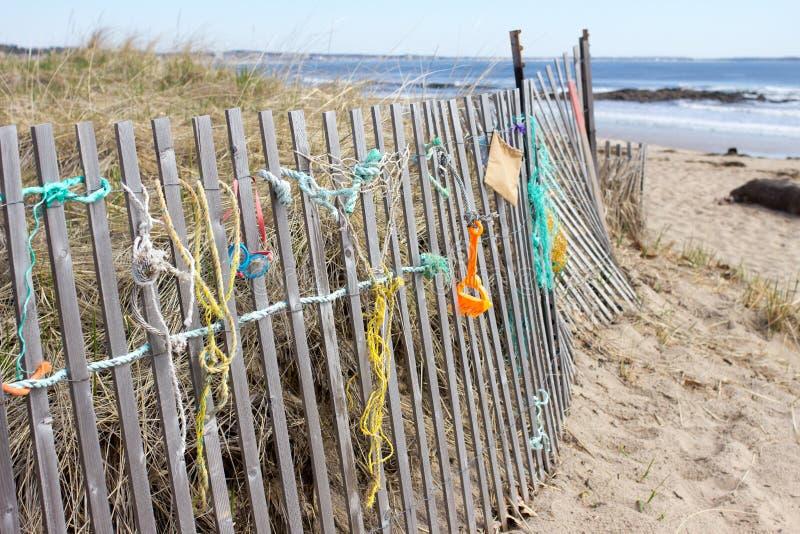 Artigos na cerca na praia do oceano imagens de stock royalty free