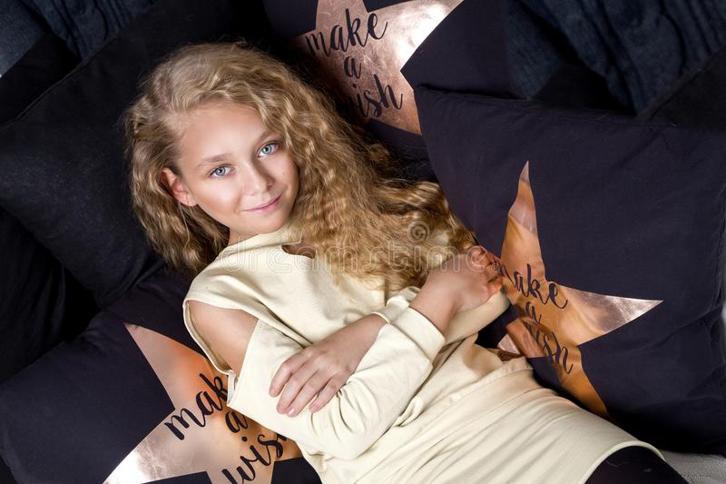 Artigt litet en ung flicka med att förbluffa ögon och blonda hår ligger på sängen och royaltyfri foto