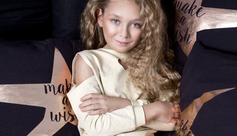 Artigt litet en ung flicka med att förbluffa ögon och blonda hår ligger på sängen och royaltyfria bilder
